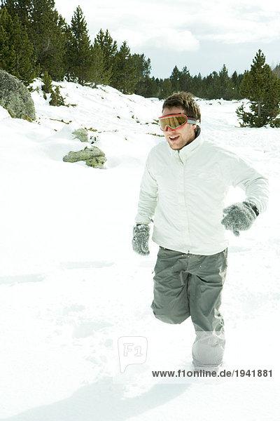 Junger Mann im Schnee  mit Skibrille  volle Länge