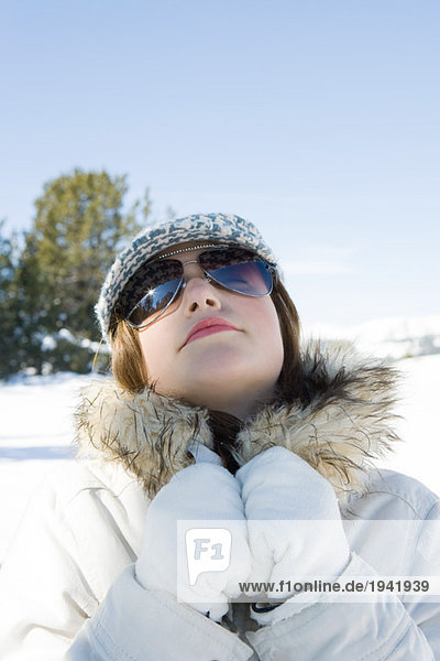 Teenage girl wearing parka and sunglasses in snow  head back  portrait