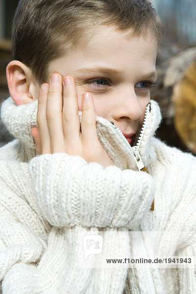 Boy holding collar of wool sweater over face  close-up  portrait