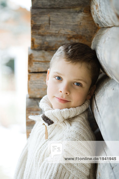 Boy leaning against wood cabin  smiling at camera