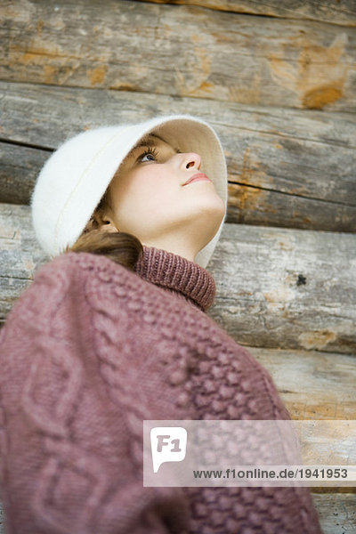 Teenage girl wearing hat and turtleneck  looking up  low angle view  portrait