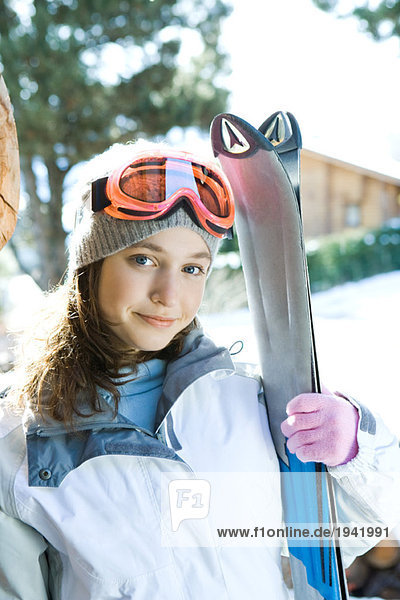 Teenage girl holding skis  portrait