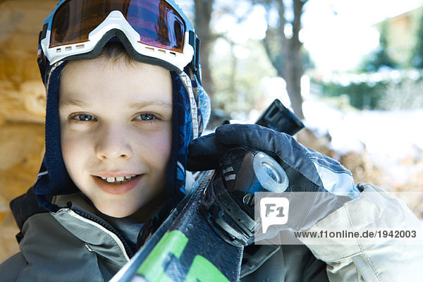 Boy holding skis on shoulder  portrait