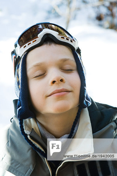 Boy in ski gear smiling with eyes closed  high angle view