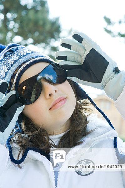 Teenage girl wearing winter clothes  adjusting sunglasses  portrait