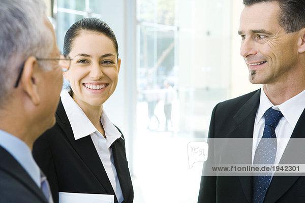 Drei Geschäftspartner im Gespräch  lächelnd