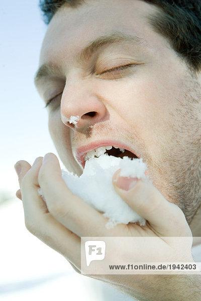 Young man eating snow  eyes closed  close-up