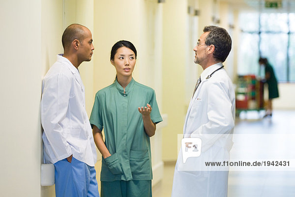 Medical staff standing in hallway  discussing  looking at each other