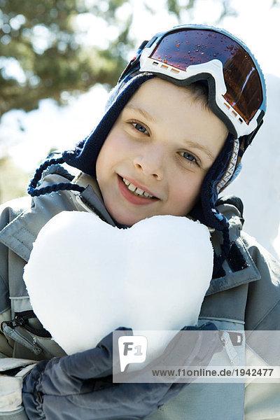 Boy in ski gear holding heart made of snow  portrait
