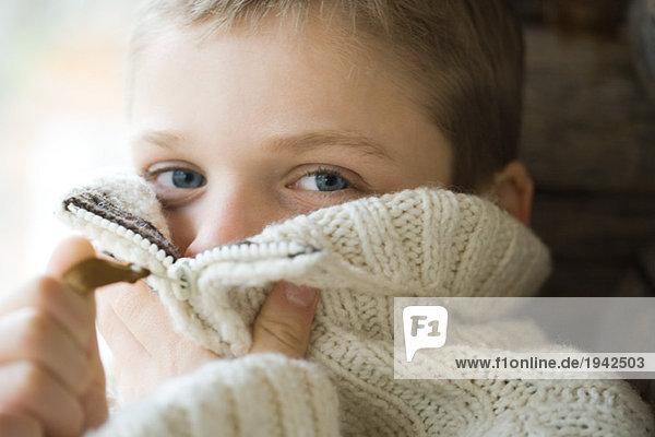 Junge Reißverschlusskragen aus Wollpullover über dem Gesicht  Nahaufnahme