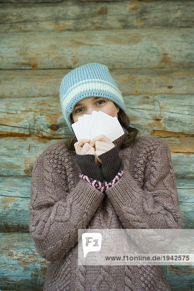 Teenage girl looking over cards  dressed in winter clothing  portrait