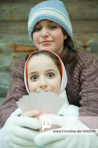 Girl holding cards  smiling at camera  friend looking at her cards  both dressed in winter clothing