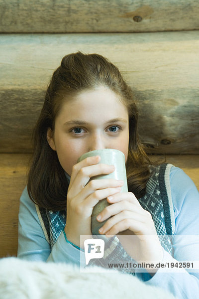 Teenage girl drinking hot beverage  looking at camera
