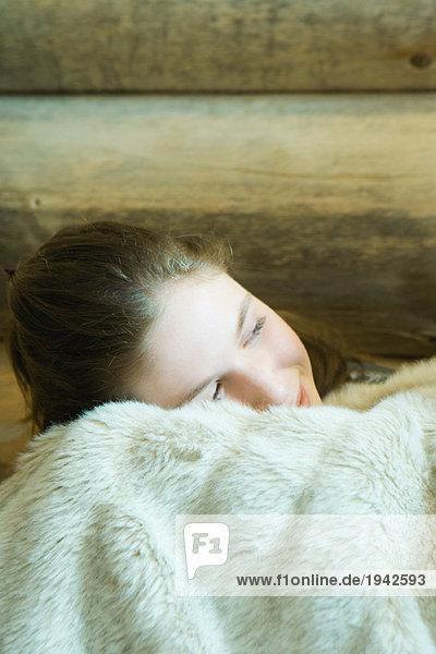 Teenage girl resting head on blanket  smiling