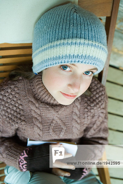 Teenage girl smiling at camera  dressed in winter clothing  high angle view