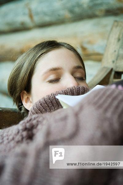 Teenage girl reclining  wearing turtleneck sweater  eyes closed