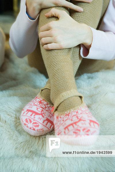 Teenagermädchen umarmt Knie  trägt Strumpfhosen und Pantoffeln  abgeschnittene Ansicht der Beine