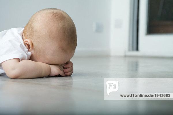 Baby auf dem Bauch liegend  Kopf auf den Armen ruhend  verdecktes Gesicht Baby auf dem Bauch liegend, Kopf auf den Armen ruhend, verdecktes Gesicht