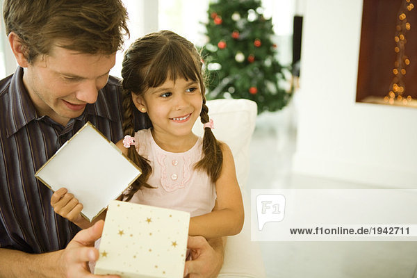 Girl sitting on man's lap  opening Christmas present  smiling