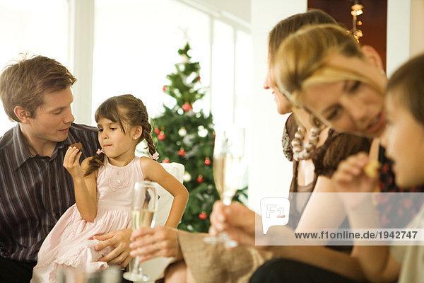 Familie sitzt zusammen  lächelt  Kinder essen Snack  Weihnachtsbaum im Hintergrund