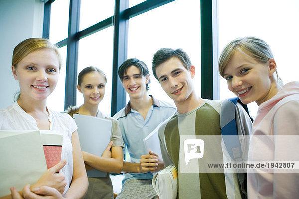 Fünf Schüler stehen vor dem Fenster  lächeln vor der Kamera  Gruppenbild