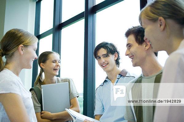 Gruppe von Schülern  die vor dem Fenster stehen  lächelnd  ein Blick auf die Kamera