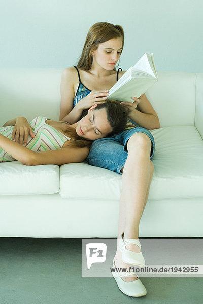 Junge Frau sitzt auf der Couch  liest Buch  Freundin ruht Kopf auf dem Schoß