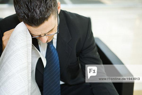 Geschäftsmann hält Finanzseite der Zeitung gegen gesenkten Kopf