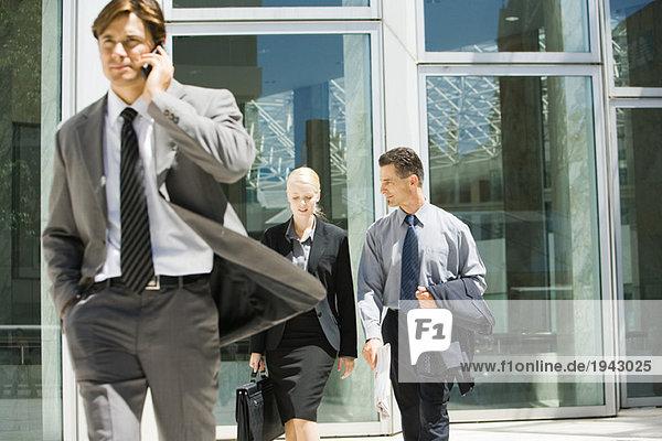 Männliche und weibliche Geschäftskollegen im Gespräch beim Verlassen des Bürogebäudes  Mann mit Handy im Vordergrund