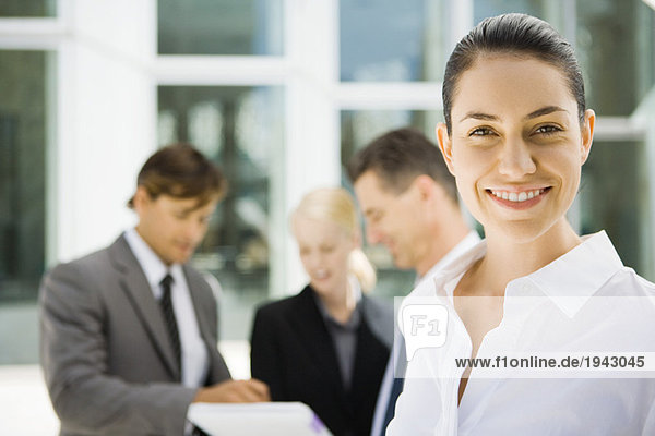 Junge Geschäftsfrau lächelt  Mitarbeiter sprechen über Vertrag im Hintergrund