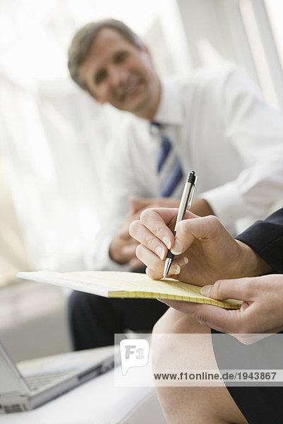 Geschäftsfrau auf Notepad schreiben