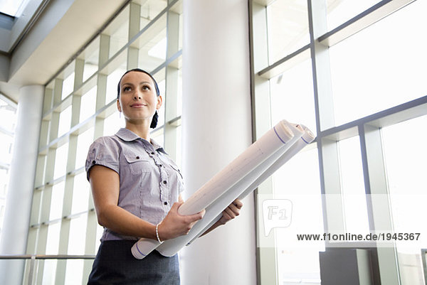 Businesswoman holding blueprints