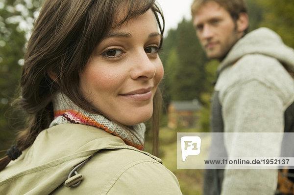 junge Frau lächelnd  Mann im Hintergrund  Nahaufnahme  Portrait