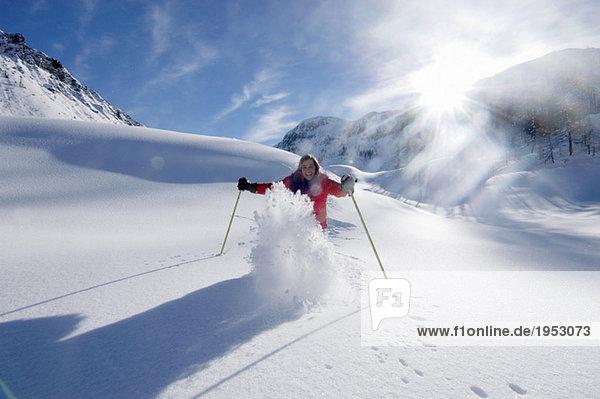 Österreich  Salzburger Land  Junge Frau beim Skifahren in den Bergen  lächeln