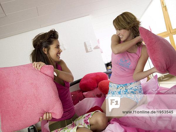 Zwei Mädchen im Teenageralter mit Kissenschlacht