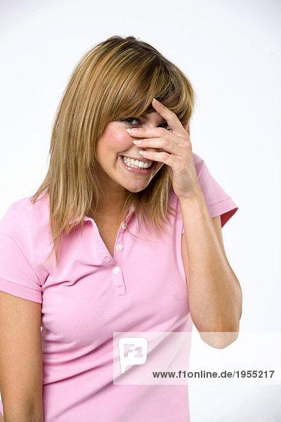 Junge Frau mit Hände über Gesicht  lächelnd