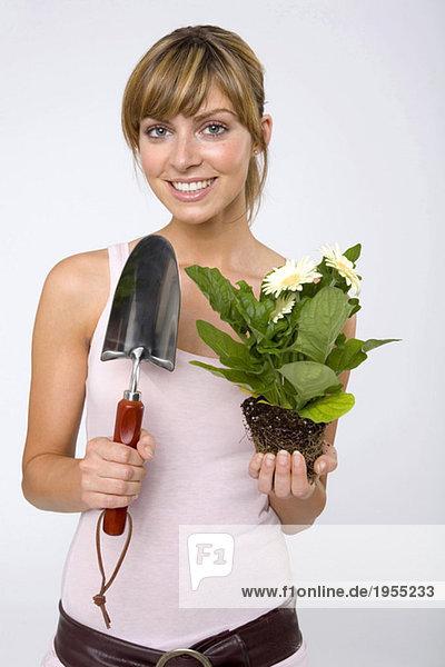 Junge Frau hält Topfpflanze und Kelle  lächelnd  Nahaufnahme