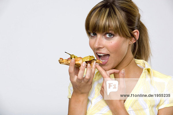 Young woman eating slice of pizza  close-up