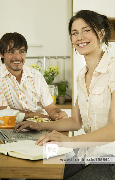 Junges Paar in der Küche  Frau mit Laptop  lächelnd