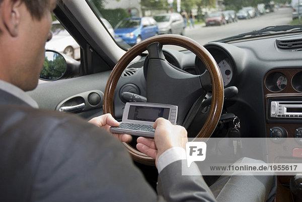 Geschäftsmann im Auto sitzend mit dem Handy  Nahaufnahme