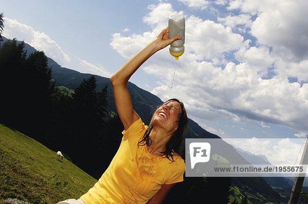Junge Frau gießt Wasser aus der Flasche ins Gesicht