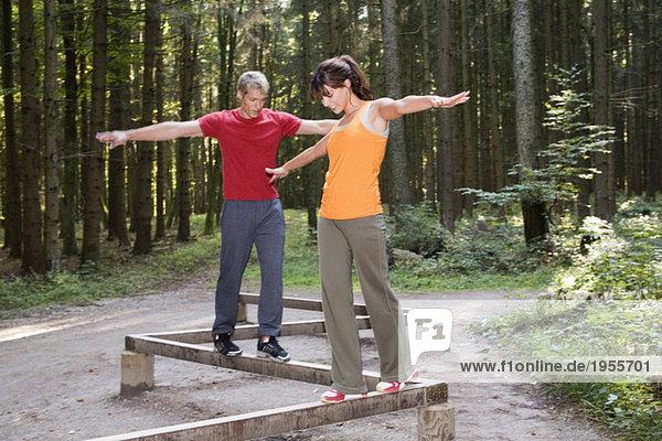 Junges Paar balanciert auf Stäben