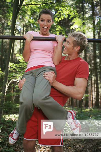 Junges Paar  das auf einer horizontalen Stange trainiert  lächelnd