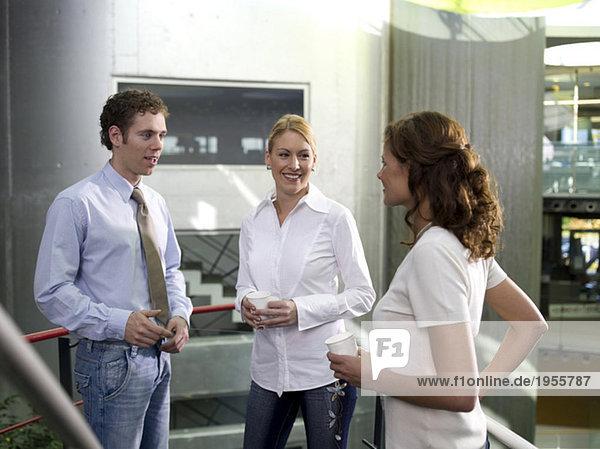 Junge Frau  die Kollegen beim Reden zuhört  lächelnd