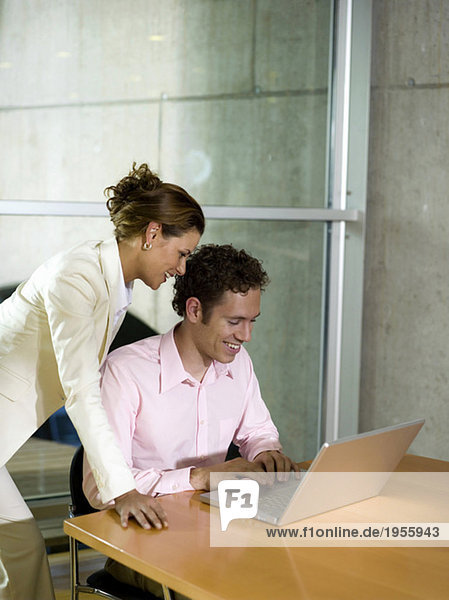 Man and woman in office  using laptop  smiling