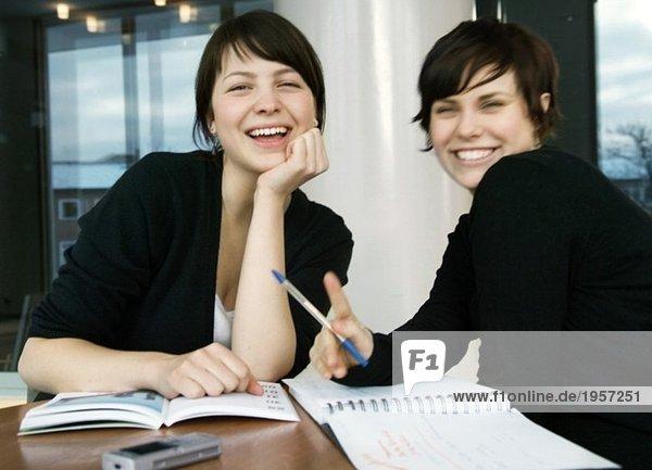 Zwei glückliche Mädchen studieren