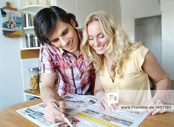 Guy und Girl beim Durchblättern von Immobilienanzeigen