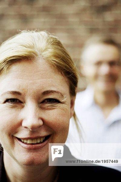 Porträt einer Frau mit Mann im Hintergrund