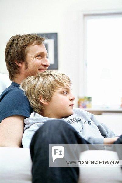 Vater und Sohn auf der Couch sitzend