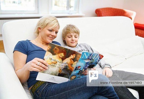 Mutter und Sohn beim Lesen auf der Couch